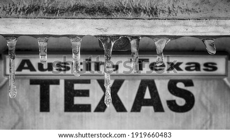 """Winter storm in Texas. Sign """"Austin, Texas"""" behind icicles. Selective focus on icicles, black and white image. Royalty-Free Stock Photo #1919660483"""