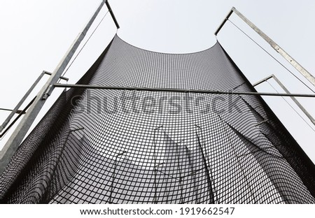 a thick strong net that restricts sports equipment and creates safety for spectators and other people, a black net on the territory of a hammer throwing sports ground Royalty-Free Stock Photo #1919662547