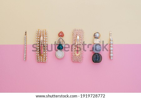 Composition of fashion accessories and hair clips for a hairstyle stylist on a pastel yellow and pink background Royalty-Free Stock Photo #1919728772