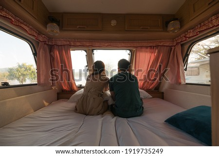 Rear of young couple sitting and taking a view on mattress inside of camper van Royalty-Free Stock Photo #1919735249