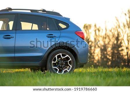 Close up of blue off road car on green grass. Traveling by auto, adventure in wildlife, expedition or extreme travel on a SUV automobile. Offroad 4x4 vehicle in field at sunrise. Royalty-Free Stock Photo #1919786660