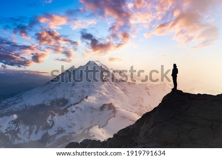 Adventure, Explore and Lifestyle Concept Composite. Adventurous Man Hiker on top of a Steep Rocky Cliff. Sunset or Sunrise. Landscape Taken from Washington, USA. Royalty-Free Stock Photo #1919791634