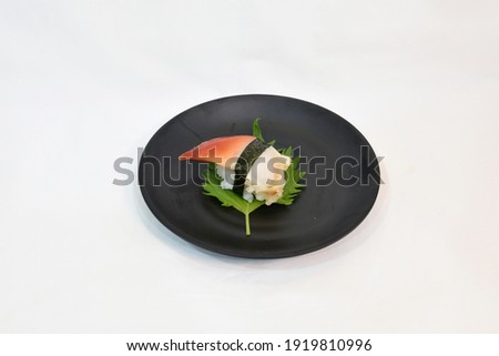 Hokkigai Sushi or Stimpson surf clam sushi on Green Shiso served in black circle ceramic plate, isolated on white background. Usable for japanese restaurant as sushi menu or buffet concept