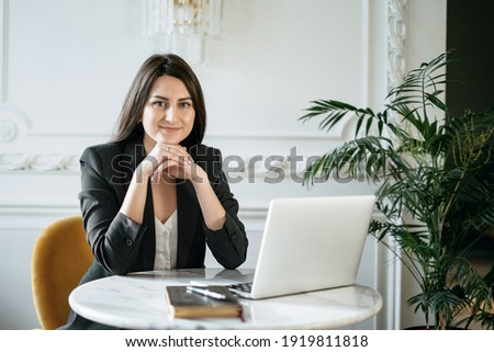 A brunette financier in a business suit. Sitting in a comfortable chair and reading an electronic textbook on a laptop. The student studies the basics of economics. Online training in a cafe. Royalty-Free Stock Photo #1919811818