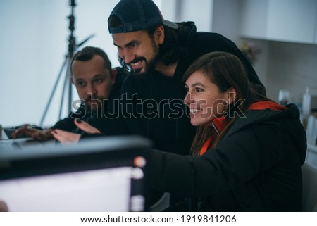Director at work on the set. The director works with a group or with a playback while filming a movie, advertising, or a TV series. Shooting shift, equipment and group. Modern photography technique.