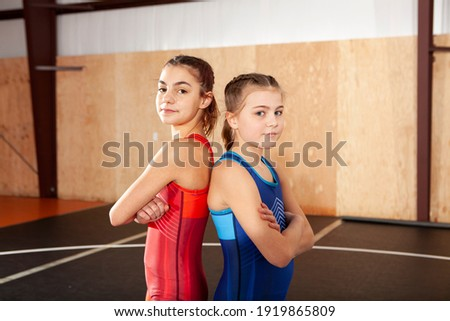 Female youth wrestling teammates in blue and red singlets