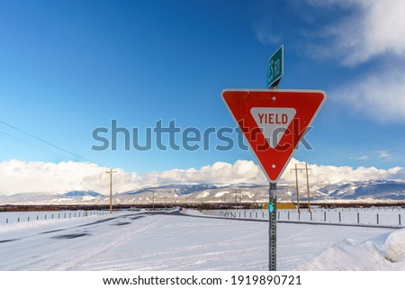 Yield Sign in Teton Valley Idaho with Sky and Snowy Winter Background