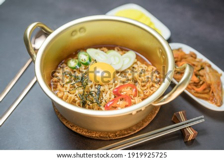 Korean style instant noodle, Ramyeon with egg yolk, chilli, kimchi vegetables pickled and radish pickles in a traditional korean noodle pot. Royalty-Free Stock Photo #1919925725