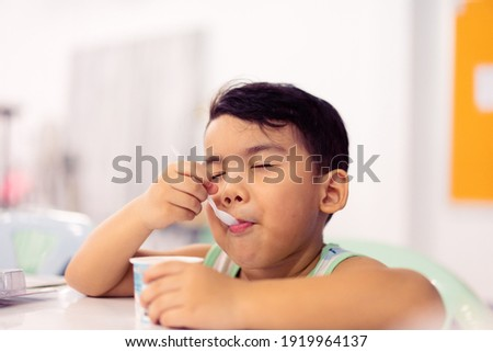 Tasty food and Delicious food concept.Portrait asian boy with spoon eat yogurt cup with milk pudding into mouth.Handsome male child boy is showing delicious.Tasty face hungry kid.boy child happy meal. Royalty-Free Stock Photo #1919964137