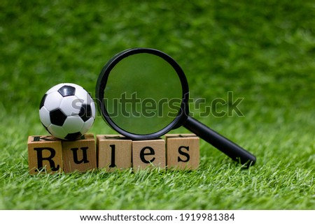 Soccer ball with magnify and word RULES are on green grass