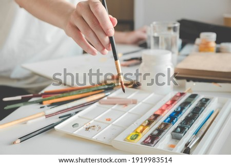 Woman painting a picture with a brush. Learning to draw at home. Autor Creating content concept.