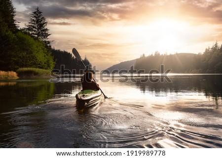 Adventurous Girl kayaking in the Pacific Ocean. Sunset Sky Art Render. Taken in San Josef Bay, Cape Scott, Northern Vancouver Island, British Columbia, Canada. Adventure Travel Concept Royalty-Free Stock Photo #1919989778