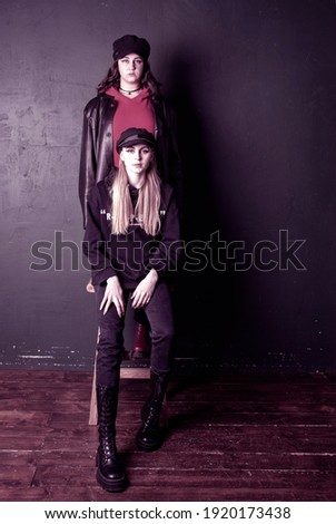 Two charming teenage girls with bright makeup, dressed in a grunge style, against a dark wall, a photo shoot in the studio. Youth trend.