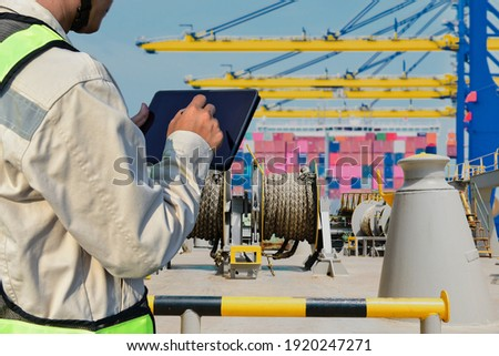 Workers with tablet in hand holding in port and Mooring winches on deck for container ship, forward mooring winch rope background Royalty-Free Stock Photo #1920247271