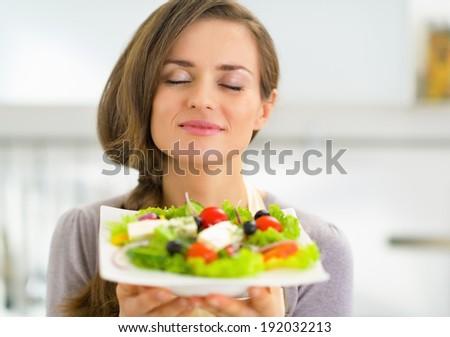 Portrait of young housewife enjoying fresh salad #192032213