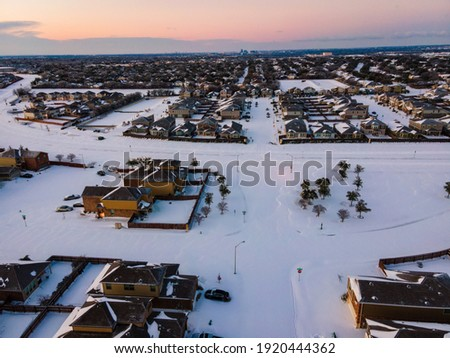 snow covered landscape above Austin Texas after winter storm Uri during morning sunrise over suburb homes  Royalty-Free Stock Photo #1920444362