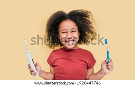 Smiling African American little girl holds manual and electric sonic toothbrushes. Child selects kind of toothbrush, isolated on pastel background