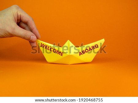 Image of businessman pushing paper made origami boat forward in a conceptual image. Words 'welcome abroad'. Over orange background with copy space. Business and onboarding concept.