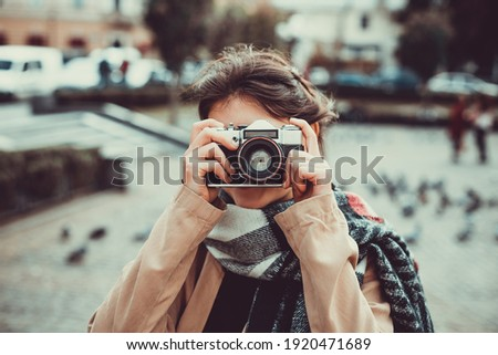 Young female tourist visiting old town on vacation and taking photos on old camera on the street.