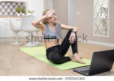 young attractive girl resting after fitness at home and looking at the laptop. quarantine fitness concept.