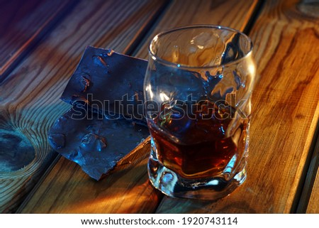A glass of cognac and a bar of chocolate on a wooden table on a dark background Royalty-Free Stock Photo #1920743114