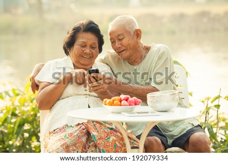 Happy asian senior couple using the mobile phone on outdoor background #192079334