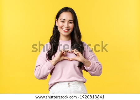 Lifestyle, emotions and advertisement concept. Lovely and caring, friendly-looking korean girl smiling broadly, showing heart sign over chest and standing yellow background