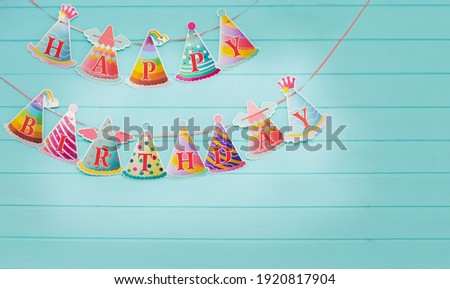 Happy birthday inscription on bright flags, on a wooden background