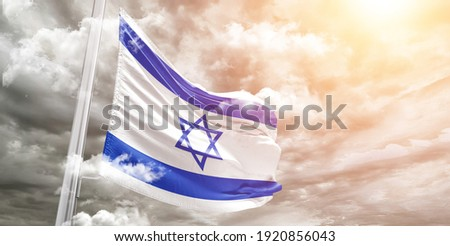 Israel national flag cloth fabric waving on beautiful grey sky.  Royalty-Free Stock Photo #1920856043
