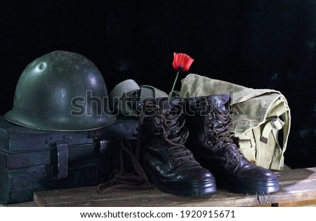 RED POPPY FLOWER INSIDE A COMBAT BOOT Royalty-Free Stock Photo #1920915671