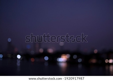 Defocused night light river veiw city scape, sky are blue and purple, image are cool tone, blurry building reflection in black and grey, light boker are white blue red  orange and yellow.