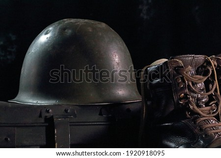 METAL ARMY HELMET WITH AN ARMY COMBAT BOOT AND A METAL TRUNK Royalty-Free Stock Photo #1920918095