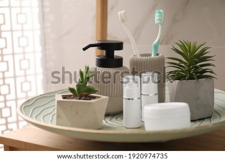 Holder with toothbrushes, different toiletries and plants on wooden table in bathroom, closeup Royalty-Free Stock Photo #1920974735