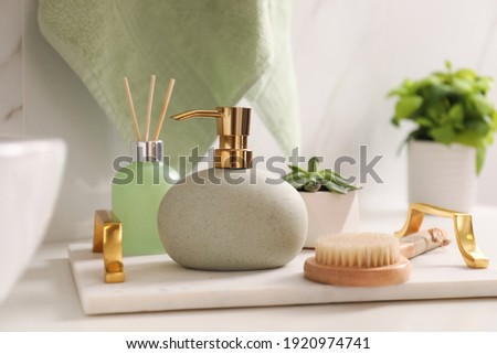 Tray with toiletries, air reed freshener and plant on countertop in bathroom Royalty-Free Stock Photo #1920974741