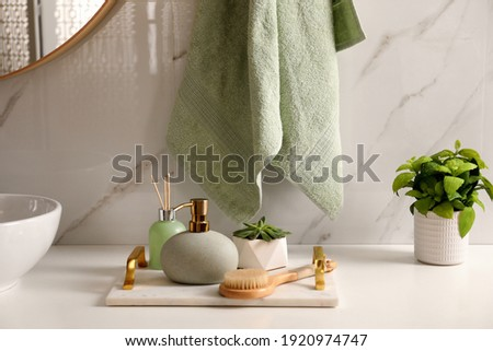 Air reed freshener, toiletries and plant near vessel sink in bathroom Royalty-Free Stock Photo #1920974747
