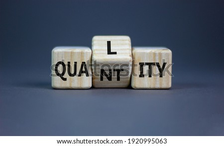 Quality over quantity symbol. Turned cubes and changed the word 'quantity' to 'quality'. Beautiful grey table, grey background, copy space. Business and quality over quantity concept.