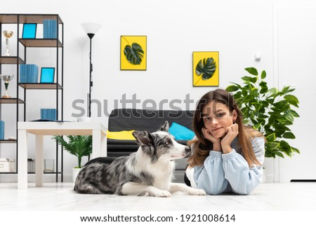 The teen and her dog lie on the floor together, relaxing in their spare time from exercising. Intelligent Border Collie Sheepdog. Modern interior design of the apartment.