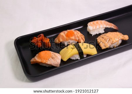 Various Sushi Set in black plate, selective focus at Burned Salmon Sushi topped with shrimp roe in the center, isolated on white background. Usable for Japanese food picture menu or Japan content