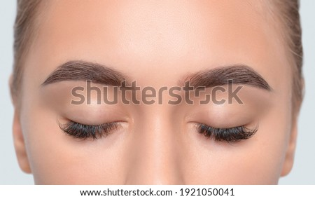 Eyebrows of a girl after plucking and cutting close-up. The make-up artist will do permanent eyebrow makeup. Makeup and cosmetology concept, eyebrow shape modeling.