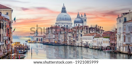 Stunning view of the Venice skyline with the Grand Canal and Basilica Santa Maria Della Salute in the distance during a dramatic sunrise. Picture taken from Ponte Dell' Accademia.