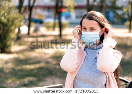 care, infants, spring, coronavirus and quarantine concept - Young cute long haired woman European Caucasian Slavic appearance put on blue medical protective mask in midday sunlight backlight in park. Royalty-Free Stock Photo #1921092815