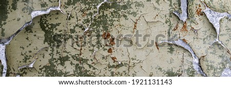 Peeling paint on the wall. Panorama of a concrete wall with old cracked flaking paint. Weathered rough painted surface with patterns of cracks and peeling. Wide panoramic grunge texture for background Royalty-Free Stock Photo #1921131143