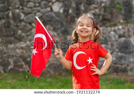 Portrait of happy little kid. Cute baby with Turkish flag t-shirt. Toddler hold Turkish flag in hand. Patriotic holiday. Adorable child celebrates national holidays. Copy space for text. Royalty-Free Stock Photo #1921132274