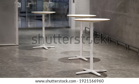 Tall table - Wooden table steel legs simplistic, tall bar stools in stylish kitchen with wooden cupboards. Royalty-Free Stock Photo #1921166960