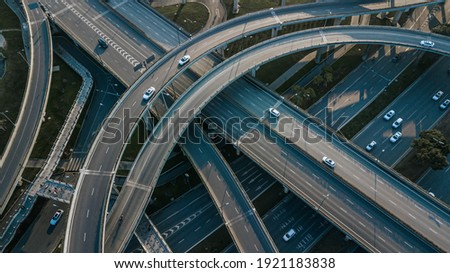 Top up aerial drone view of elevated road and traffic junctions in Chinese metropolis city Chengdu during sunny day. Modern construction design of traffic ways to avoid traffic jams. Few vehicles. Royalty-Free Stock Photo #1921183838