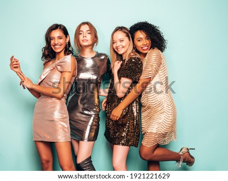 Four young international beautiful brunette women in trendy summer  shiny dress.Sexy smiling carefree female posing near blue wall in studio.Fashionable models with bright evening makeup Royalty-Free Stock Photo #1921221629