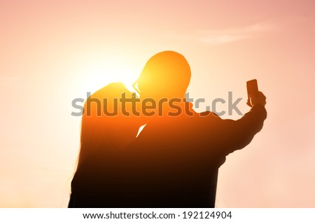 Couple kissing themself at sunset while taking a selfie with phone