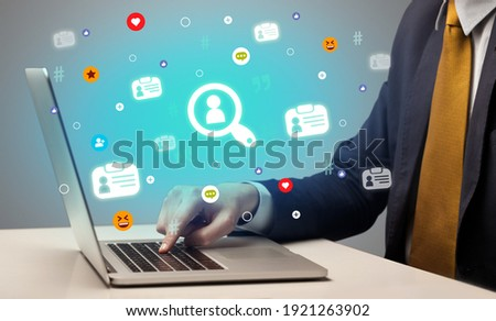 Hand surfing on the social media with lookup icons coming out from the screen, networking concept