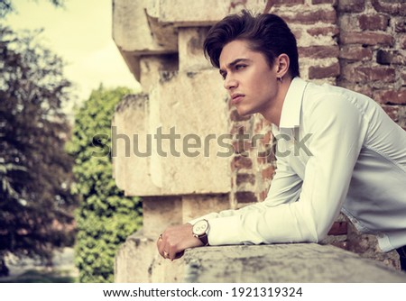 One handsome elegant young man in urban setting in European city, standing in sunny day Royalty-Free Stock Photo #1921319324