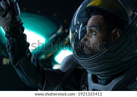 Portrait of African American Black male astronaut inside spaceship cockpit. Sci-fi space exploration concept. Mars mission Royalty-Free Stock Photo #1921325411